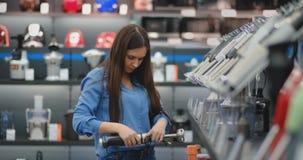 В кухонных приборах магазина приборов, женщина брюнета в голубой рубашке комплектует blender в ее руках и рассматривает видеоматериал
