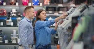 В кухонных приборах магазина приборов, пара выбирает blender в их руках и рассматривает дизайн и видеоматериал