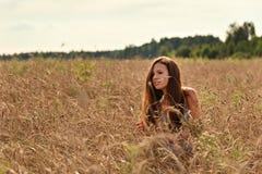 В лучах спокойного захода солнца вечера на пшеничном поле за колосками девушка в ретро платье стоковая фотография rf