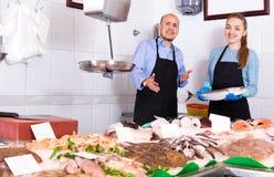 В магазине предлагая продавца улыбки свежих рыб Стоковые Изображения RF