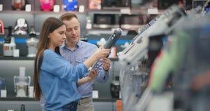 В магазине приборов, женатая пара в ежедневных одеждах выбирает blender для приобретения путем просмотр и удержание видеоматериал