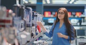 В магазине приборов, женщина брюнета в рубашке выбирает blender для ходить по магазинам путем осматривать и держать прибор внутри видеоматериал
