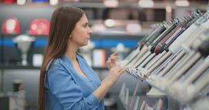 В магазине приборов, женщина брюнета в рубашке выбирает blender для ходить по магазинам путем осматривать и держать прибор внутри акции видеоматериалы