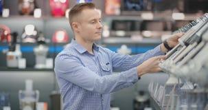 В магазине приборов, человек в рубашке выбирает blender для покупки путем просмотр и удержание прибора видеоматериал