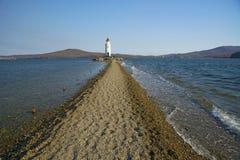 В море заполненном дороге к маяку, в середине линии пляжа моря проходит стоковые изображения