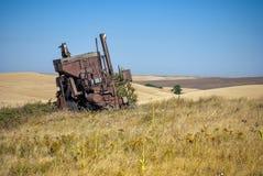 В море пшеницы старый зернокомбайн ржавеет стоковое изображение