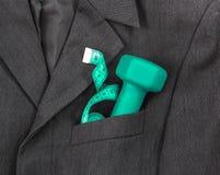 В нагрудном кармане темной куртки ` s чернокожего человека в светлой гантели зеленого цвета сантиметра ленты спортивного инвентар Стоковое фото RF