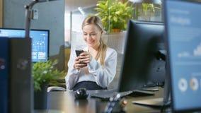 В офисе красивая коммерсантка использует ее мобильный телефон и стоковые изображения