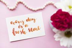 Вдохновляющая цитата каждый день новый старт написанный в стиле каллиграфии с акварелью Состав на розовой предпосылке fla Стоковые Изображения