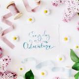 Вдохновляющее ` цитаты ежедневное новое ` приключения написанное в стиле каллиграфии на бумаге с рамкой венка с сиренью и стоцвет Стоковые Изображения RF
