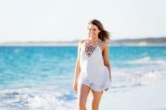 вдоль детенышей женщины пляжа гуляя Стоковые Изображения