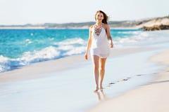 вдоль детенышей женщины пляжа гуляя Стоковое фото RF
