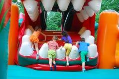 В парке атракционов, раздувное скольжение для детей взбирается. Стоковое Изображение RF