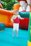 В парке атракционов, скача на раздувную девушку скольжения. Стоковое фото RF