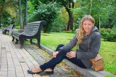 В парке, девушка сидя на обочине Стоковое Изображение
