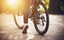 В парке на дороге девушка с велосипедом и идет ехать на ей стоковая фотография rf
