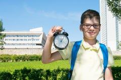 В парке, в свежем воздухе, конец-вверх, студент держит будильник в его руках и улыбках что полдень стоковая фотография rf