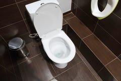 В плитке коричневого цвета общественного туалета, белое взгляд сверху шара туалета Стоковая Фотография