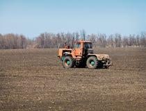 В поле двигает старый трактор стоковые изображения rf