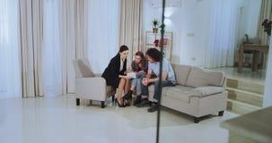 В просторном современном агенте недвижимости дома показывая к красивой молодой паре план дома они очень сконцентрированы акции видеоматериалы