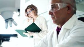 В работе человека лаборатории медицинского университета с микроскопом сток-видео