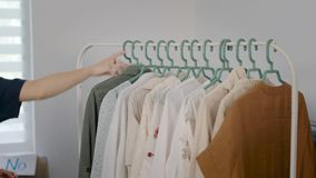 В рамке рук женщины, идя через одежды Одежды вися на вешалке, платья, рубашки, блузки и сток-видео