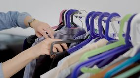 В рамке рук женщины, идя через одежды Одежды вися на вешалке, платья, рубашки, блузки и видеоматериал