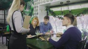В ресторане официант принимает заказ от группы в составе друзья сток-видео