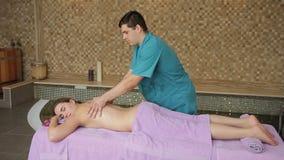 В салоне курорта человек в форме делает массаж для женщины лежа на кресле сток-видео