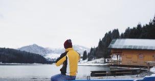 В середине большого озера и рядом с деревянного человека дома имейте время раздумья, сидящ на голубой шлюпке и восхищайтесь видеоматериал