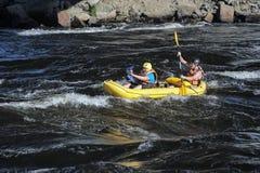 2 в спасательных жилетах и весельной лодке шлемов Стоковая Фотография