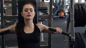 В спортзале красивая женщина выполняет жим лёжа от комода сток-видео