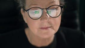 В стеклах зрелой женщины показывает newsline пока она смотрит через социальные средства массовой информации видеоматериал