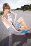 В стиле фанк молодое белокурое усаживание на ее скейтборде стоковая фотография rf
