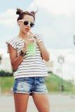 В стиле фанк питьевая вода девушки против неба Стоковое Изображение