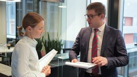 В стойке человека и женщины офиса в коридоре и обсудите проект на бумаге видеоматериал