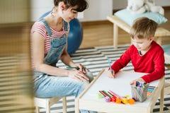 В терапии, ребенк учит навыки которые не приходят естественно из-за ADHD, как слушать и оплачивать внимание лучше стоковое фото rf