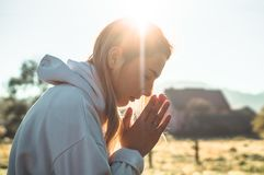 В утре девушка закрыла ее глаза, моля outdoors, руки сложенные в концепции молитве для веры, духовности, концепции вероисповедани стоковая фотография