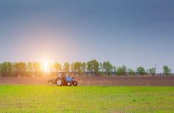 В утре на восходе солнца трактор едет для того чтобы вспахать поле Стоковая Фотография