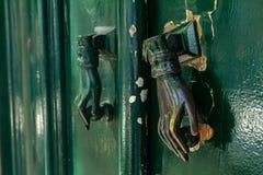 в форме Рук knocker двери на зеленой двери стоковые фотографии rf