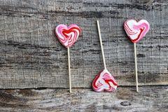 3 в форме сердц бело-красных леденца на палочке на деревянной поверхности Стоковое Изображение