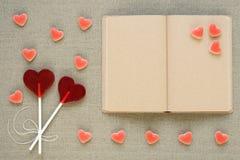 в форме Сердц леденцы на палочке, конфеты и старый дневник Стоковые Фотографии RF