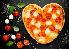 в форме Сердц пицца с томатами вишни, моццареллой и базиликом дальше Стоковая Фотография