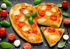 в форме Сердц пицца с томатами вишни, моццареллой и базиликом дальше Стоковые Изображения