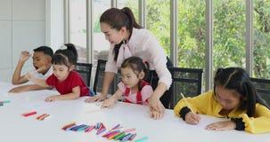 В художественном классе, азиатские студенты рисуют сознательно видеоматериал