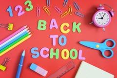 В центре красной предпосылки, надпись НАЗАД К ШКОЛЕ, сделанной в покрашенных письмах Яркая покрашенная школа Стоковое фото RF
