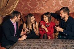 2 влюбчивых пары празднуя совместно на ресторане Стоковые Изображения RF