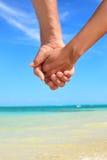 Влюбленность - романтичная пара держа руки на пляже Стоковое фото RF