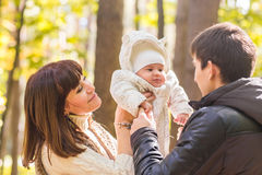 Влюбленность, родительство, семья, сезон и концепция людей - усмехаясь пары с младенцем в осени паркуют стоковое фото rf