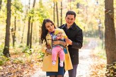 Влюбленность, родительство, семья, сезон и концепция людей - усмехаясь пары с младенцем в осени паркуют стоковая фотография